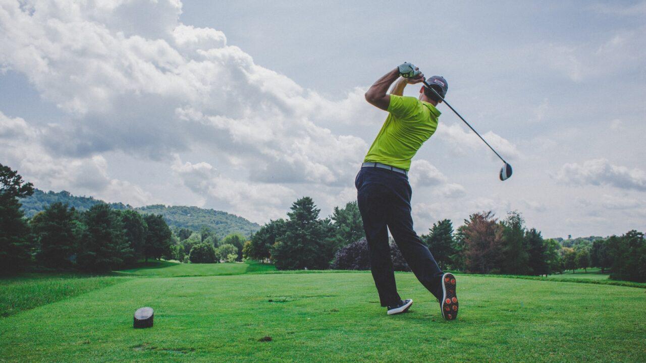 photo of man swinging golf driver
